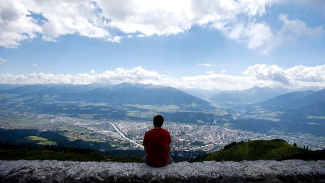 A man sits on a wall as he enjoys the view on the western Austrian city of Innsbruck during a hot summer day in Innsbruck
